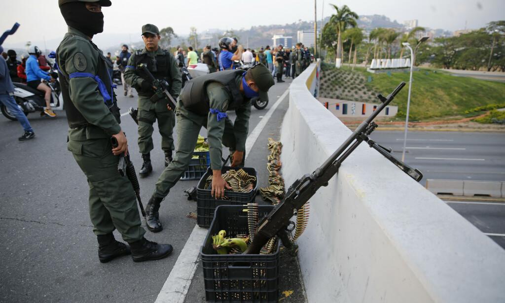Soldater inntar stillinger på ei bru nær flybasen La Carlota. Foto: AP / NTB scanpix