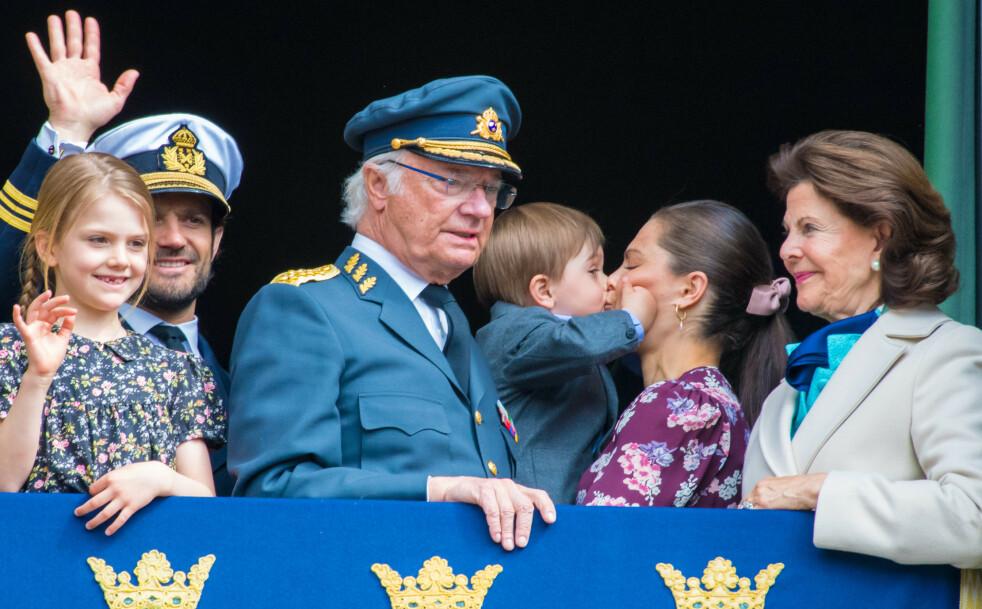 KOS I KULISSENE: Mens prinsesse Estelle, prins Carl Philip, jubilanten kong Carl Gustaf og dronning Silvia vinket til folket, benyttet prins Oscar anledningen til å vise hvor glad han er i mamma Victoria. FOTO: NTB Scanpix