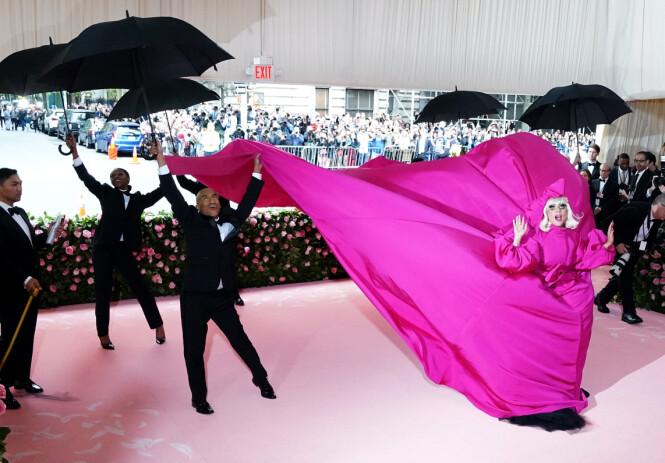 SKIFTET: Med hjelp fra en rekke mennesker tok Gaga av seg den rosa kjolen midt på løperen. Foto: Scanpix