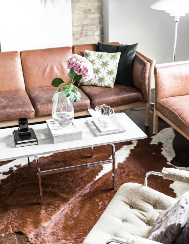 Det er ikke bare samspillet mellom det rå og det feminine som gjør leiligheten interessant. Også ulike materialer, som varme konjakknyanser på skinn og tre mot kjølig krom og marmor, skaper spennende motsetninger.