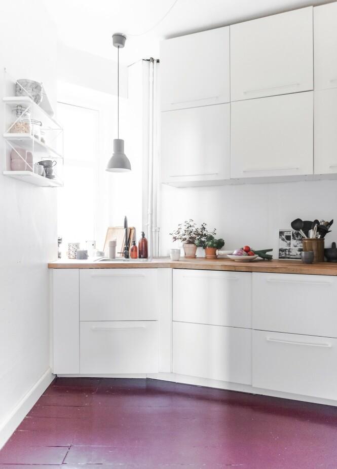 Det hvite kjøkkenet ble brutt opp med en dyp farge på gulvet. De har malt tre strøk med tremaling fra Flügger, noe som til nå har holdt veldig godt, forteller paret. Foto: Benjamin Lee Rønning Lassen