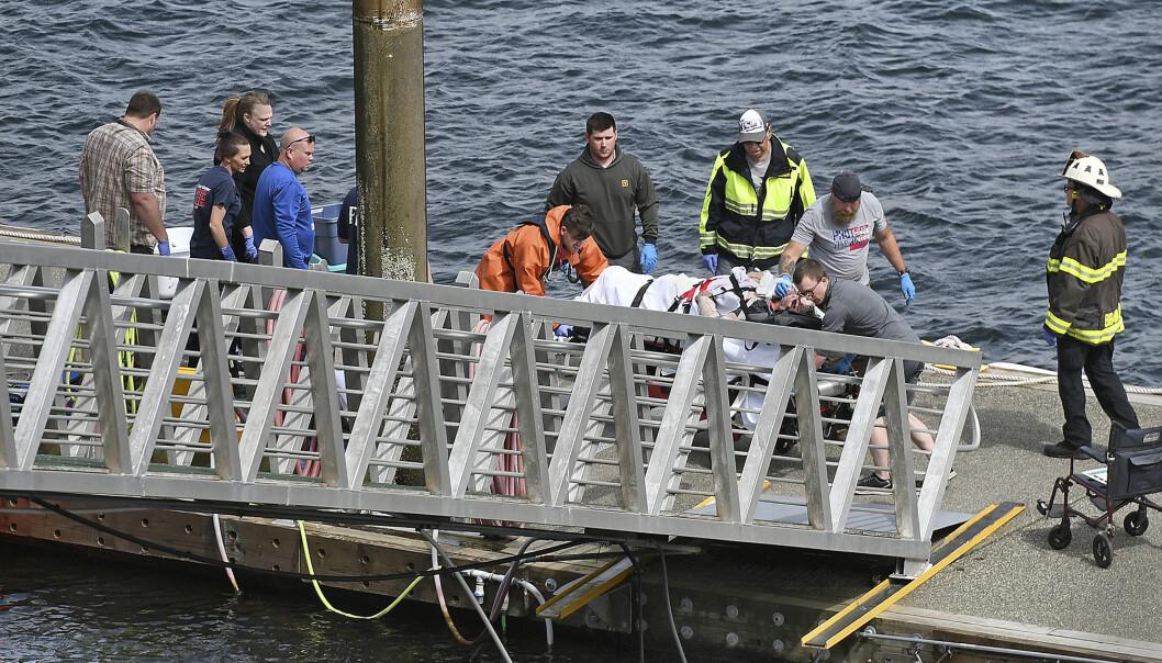 Hjelpemannskaper med en skadet person fra flykrasjet i Ketchikan i Alaska i USA. Foto: NTB scanpix/ AP