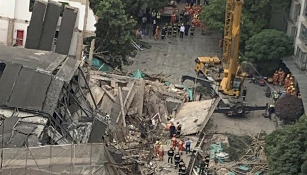 Minst fem mennesker er funnet døde etter at et to etasjer høyt næringsbygg raste sammen i Shanghai torsdag formiddag. Foto: AP / NTB scanpix.