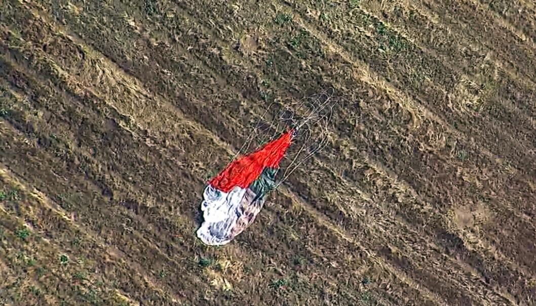Pilotens fallskjerm ligger etterlatt på et jorde. Han overlevde etter å ha skutt seg ut av F-16-flyet før det styrtet i en lagerbygning. Foto: KABC-TV / AP / NTB scanpix
