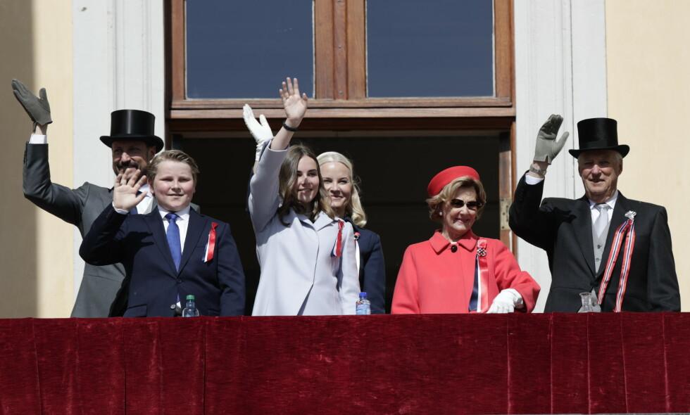 HILSER PÅ FOLKET: Kronprins Haakon, prins Sverre Magnus, prinsesse Ingrid Alexandra, kronprinsesse Mette-Marit, dronning Sonja og kong Harald er på plass på slottsbalkongen for å hilse på barnetoget. Foto: NTB Scanpix