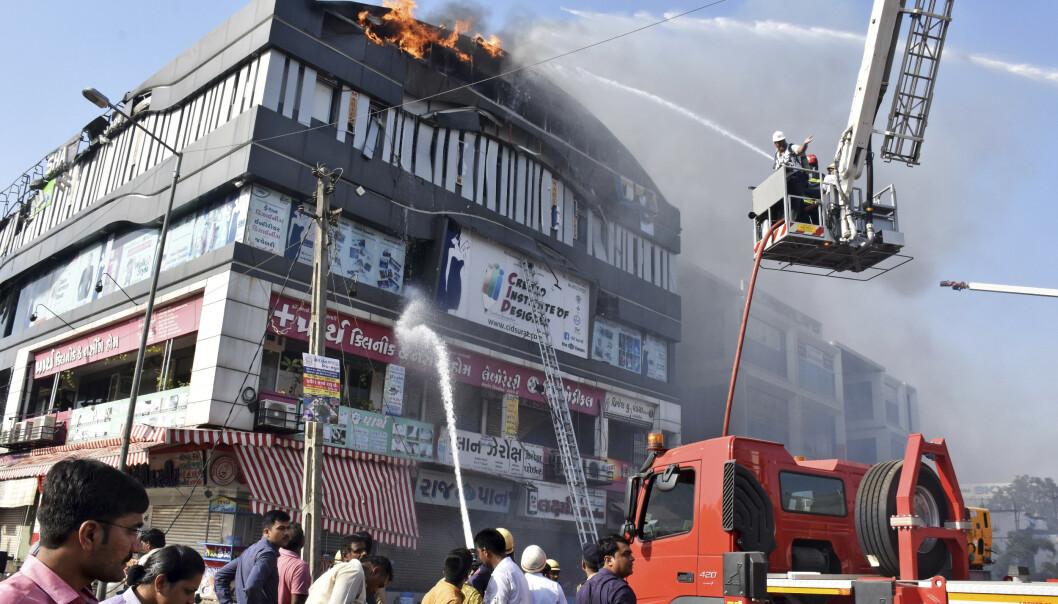 Brannmannskaper kjemper mot flammene i en bygning der det ble holdt undervisningstimer for skoleelever i byen Surat i den indiske delstaten Gujarat. Foto: Sarju Parekh / AP / NTB scanpix