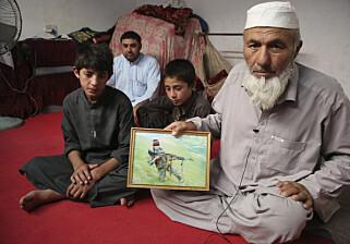 MISTET SØNNEN: Noor Mohammad og familien flyktet fra landsbyen sin i slutten av april, da IS kom dit. Han viser fram bilde av sønnen sin, som ble drept. Foto: Rahmat Gul / Ap / Scanpix