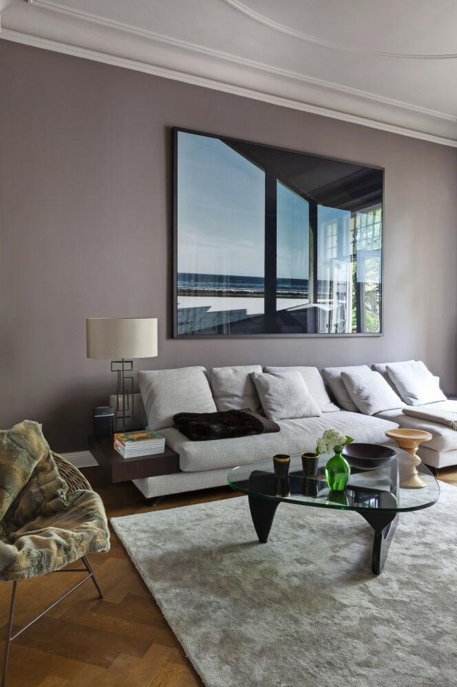 En farget vegg gir en fin kontrast til den lyse sofaen, som er designet av Rodolfi Dordoni for Minotti. Sofabordet er designet av Isamu Noguchi, bordlampen er fra Porta Romana, og bildet over sofaen er av Werner Pawlok. FOTO: Anne-Catherine Scoffoni