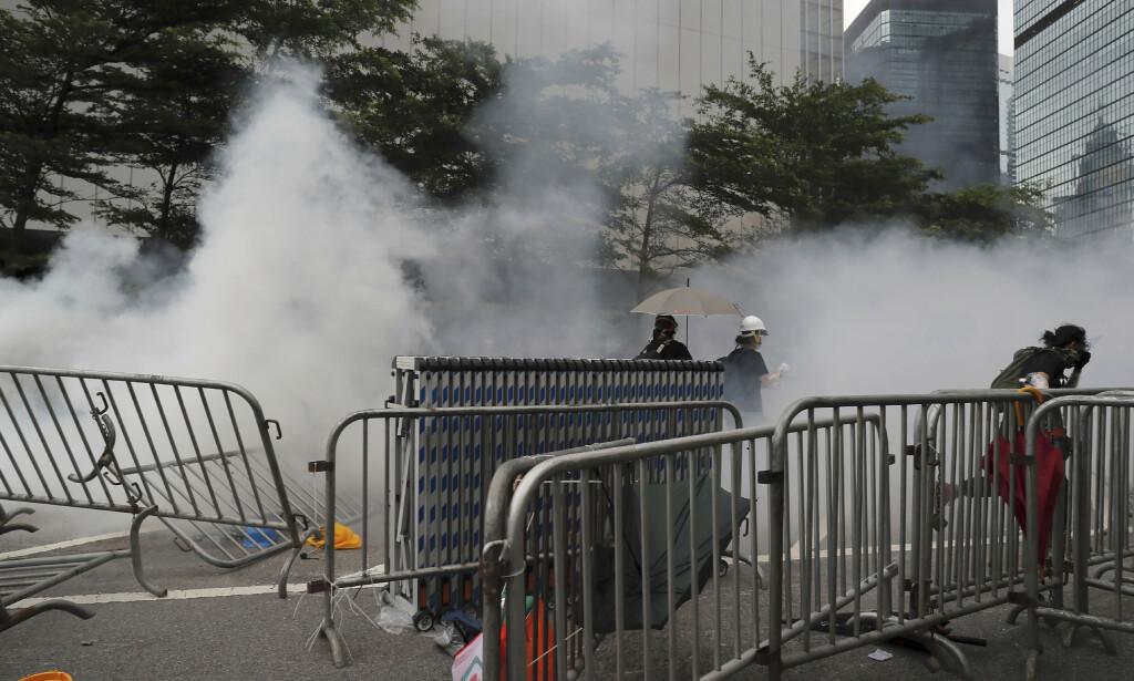 Skyer med tåregass sendte demonstranter på flukt utenfor den lovgivende forsamlingen i Hongkong onsdag. Foto: AP / NTB scanpix