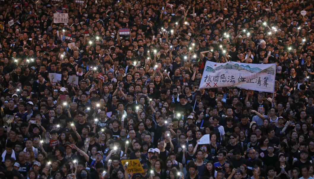Mobiltelefonlykter lyser opp demonstrasjonen i Hongkong søndag. Foto: Vincent Yu / AP / NTB scanpix