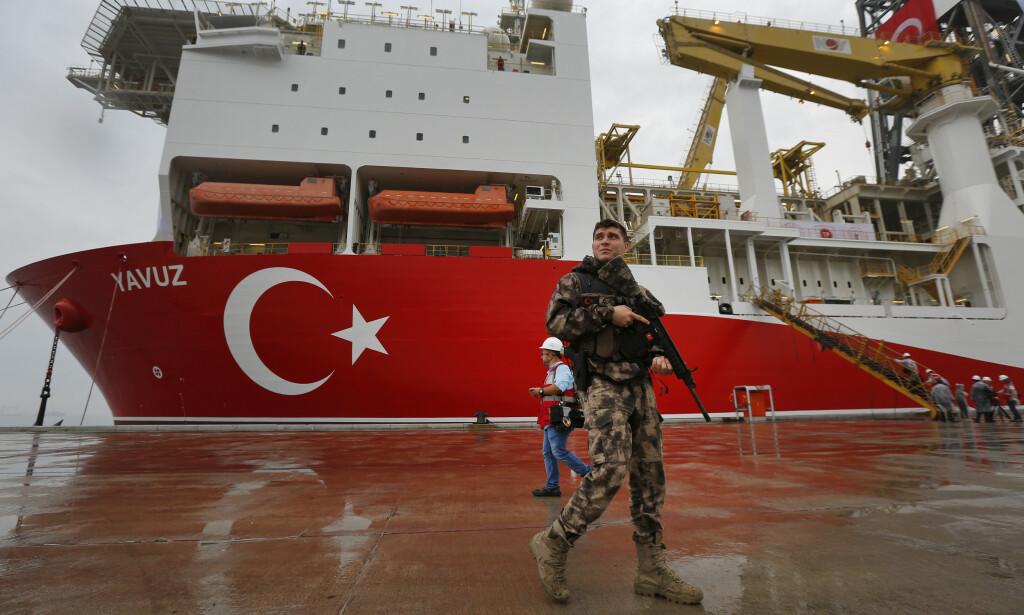En politimann hoder vakt foran det andre boreskipet Tyrkia sender til farvannet utenfor Kypros for å lete etter olje og gass. Foto: Lefteris Pitarakis / AP / NTB scanpix