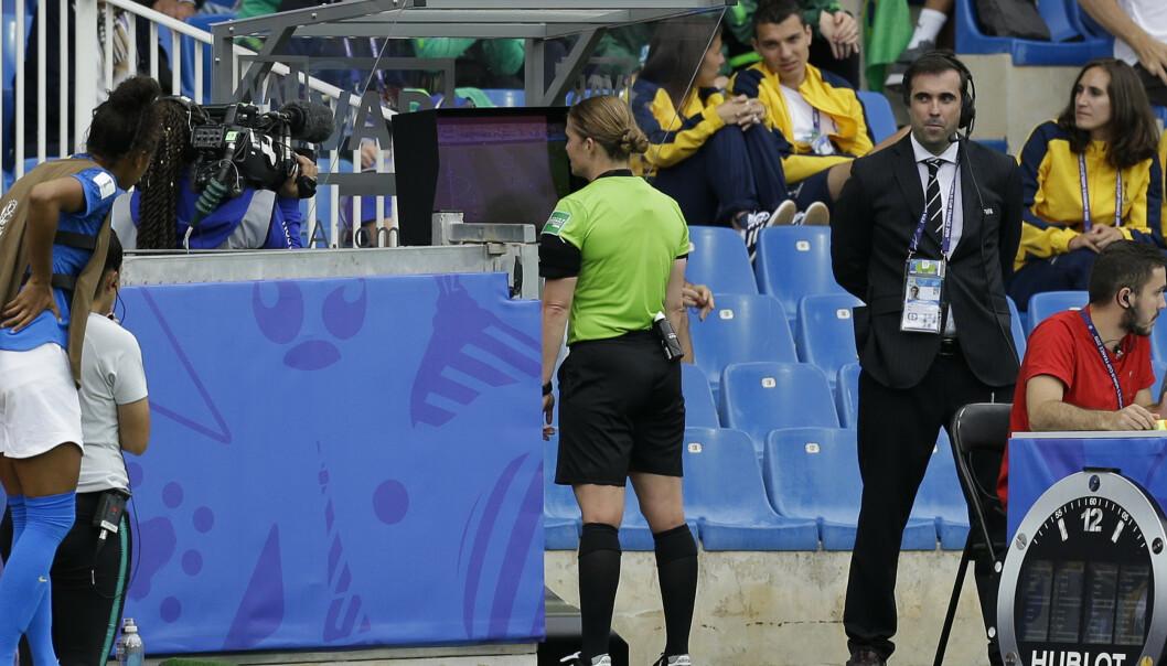 <strong>VAR:</strong> Esther Staubli fra Sveits ser på VAR-skjermen under kampen mellom Australia og Brasil på Stade de la Mosson i Montpellier i Frankrike. Foto: AP Photo/Claude Paris