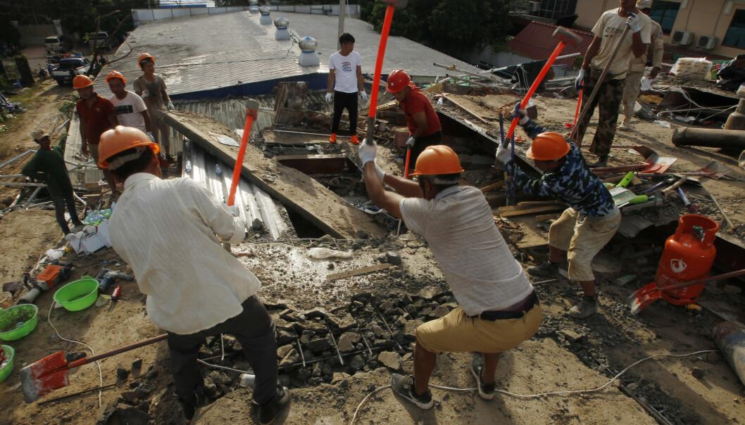 Redningsarbeidere jobber stålsager for å med å finne overlevende i ruinene etter at en sju etasjer høy blokkk raste sammen Preah Sihanouk provinsen i Kambodsja. Foto: Heng Sinith /AP Photo/ NTB scanpix
