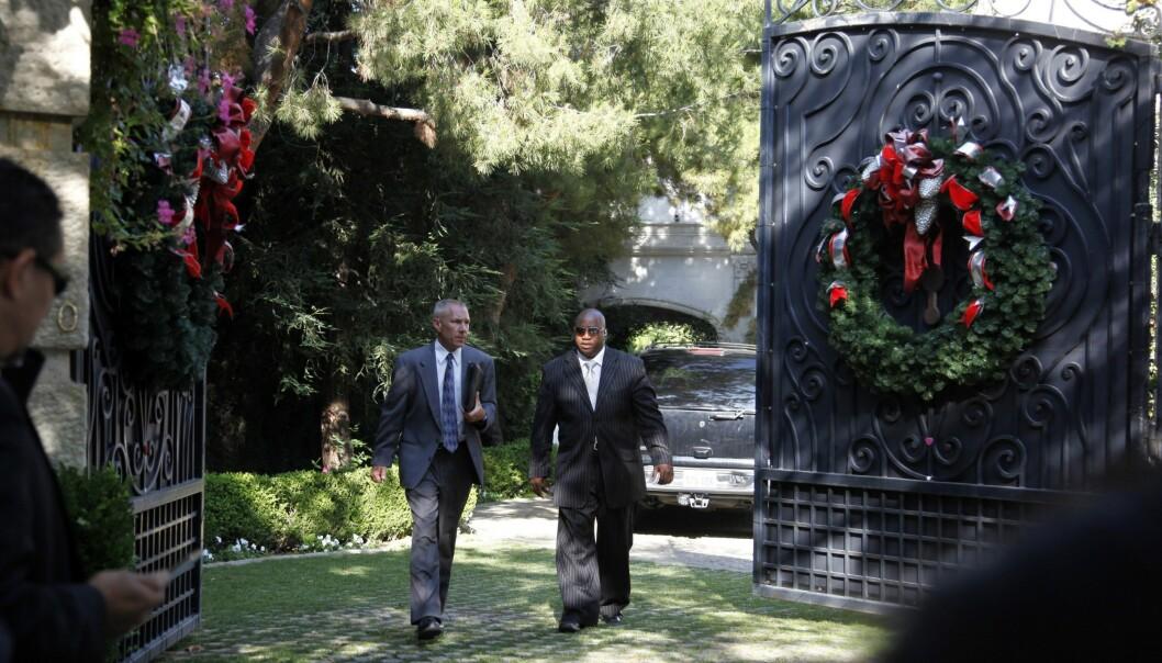<strong>DEN GANG DA:</strong> Etterforskere avbildet på vei ut av eiendommens port samme dag som Michael Jackson døde. Foto: NTB Scanpix