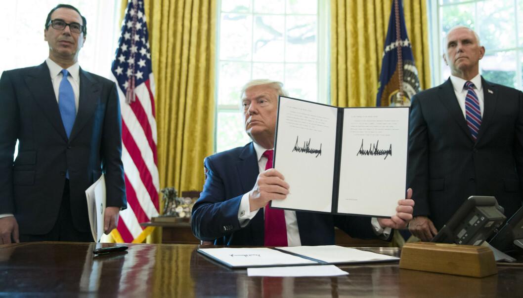 President Donald Trump viser fram presidentordren om nye sanksjoner mot Iran i Det ovale kontor mandag. Sammen med ham står finansminister Steven Mnuchin (til venstre) og visepresident Mike Pence. Foto: Alex Brandon / AP / NTB scanpix