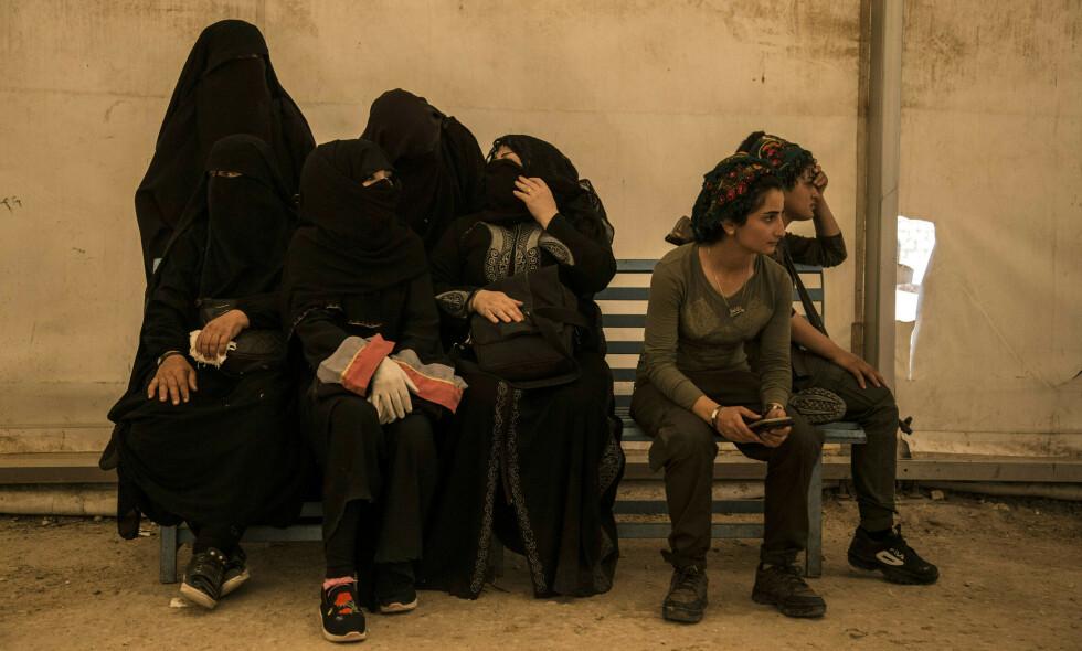 FRIE: Kvinnene kledd i svart skal være kvinner som er i slekt med IS-krigere, og venter på å komme bort fra den overfylte al-Hol-leiren. Derfra drar også de to kvinnene fra den kurdiske hæren Syrian Democratic Forces (SDF), som kontrollerer leiren. Foto: Baderkhan Ahmad / Ap / Scanpix