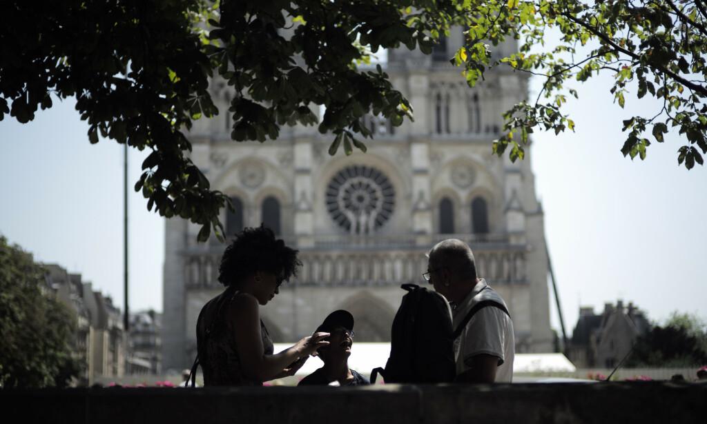 Turister tar seg en pause under et tre foran Notre-Dame onsdag. Foto: Kamil Zihnioglu / AP / NTB scanpix