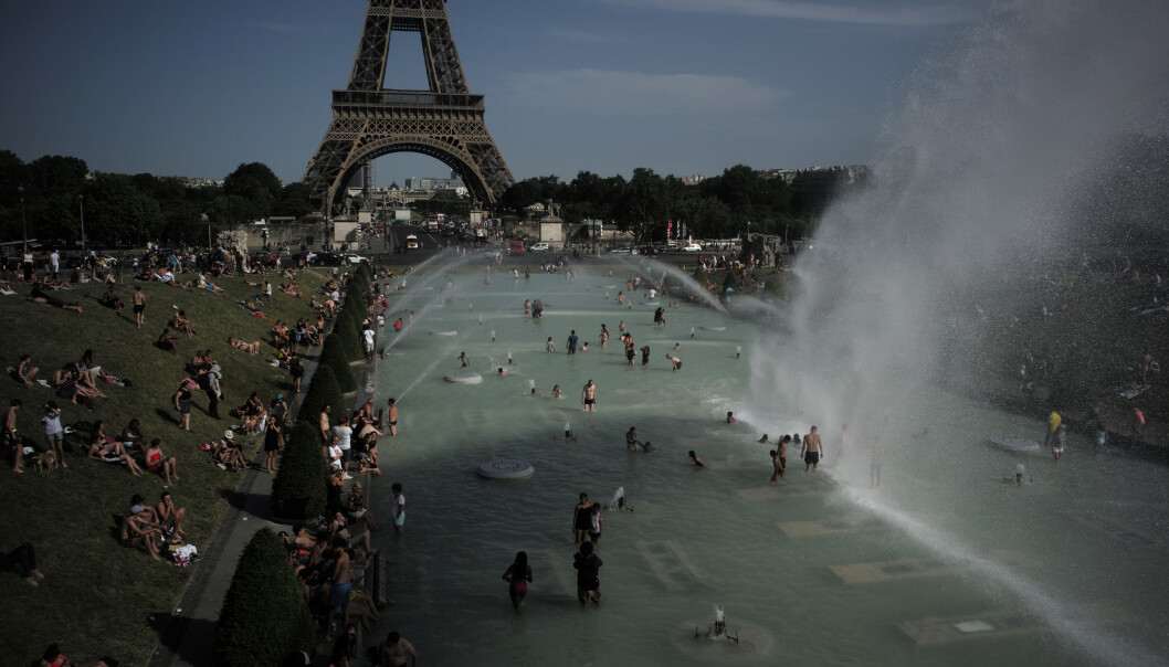 Varme franskmenn kjøler seg ned i fontenene ved Eiffeltårnet i Paris. Foto: AP / NTB scanpix