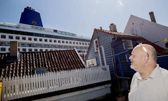 <strong>FRA BAKGÅRDEN:</strong> Bernt Posch sitter heller i bakgården, der han er mer skjermet fra skipene og turistene. Likevel titter skipet opp. Foto: Kristian Ridder-Nielsen / Dagbladet