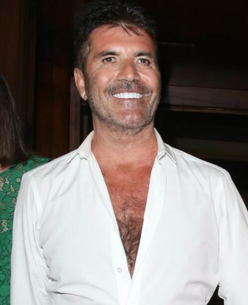 STORT GLIS: Simon Cowell smilte bredt til de oppmøtte fotografene på vei hjem fra den nylige sommerfesten. Foto: NTB Scanpix