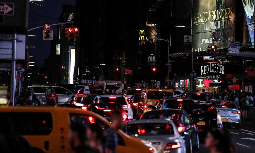 KAOS: Det meldes om at fotgjengere forsøker å hjelpe å dirigere trafikken i New York etter at et strømbrudd har mørklagt store deler av Manhattan. Foto: Jeenah Moon / Reuters / NTB Scanpix