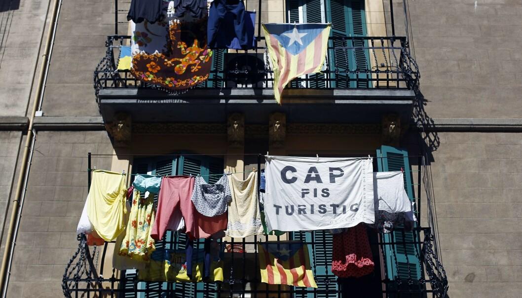 <strong>INNVANDRINGSTAK:</strong> På en balkong i bydelen Barceloneta i Barcelona henger et krav om tak på antallet korttidsutleide leiligheter. Innbyggerne vil ha en slags innvandringsstopp for rike utlendinger som ødelegger byen under sine kortvarige opphold. Foto: Quique García / AFP / NTB Scanpix