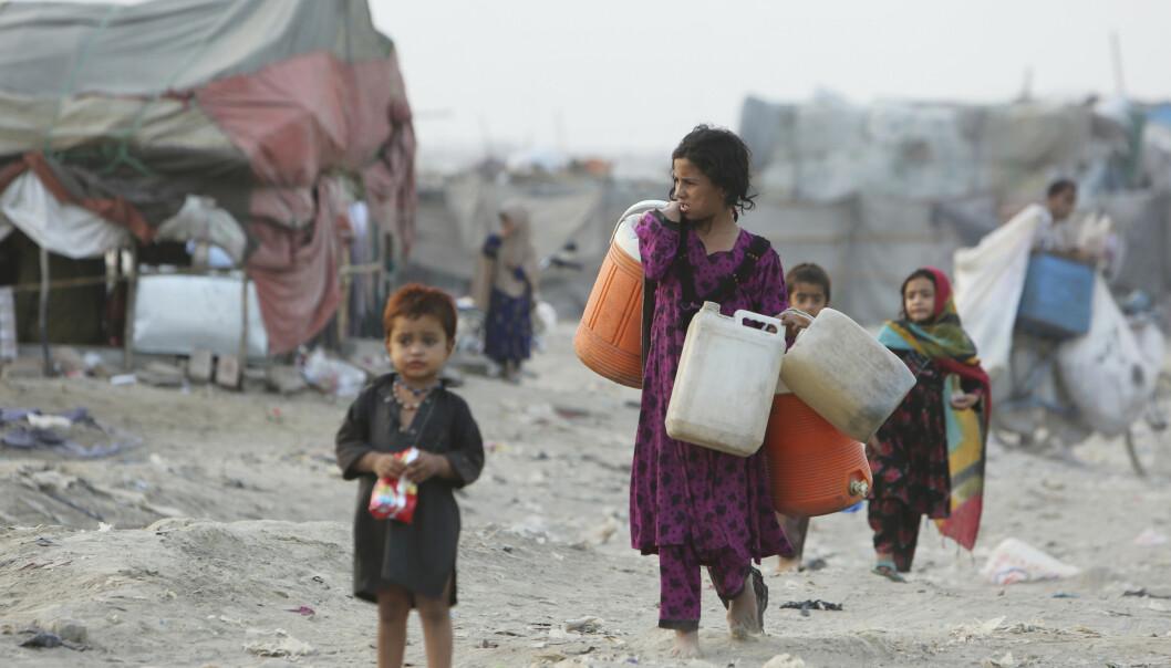Afghanere som har reist fra sitt hjemland på grunn av krig og hungersnød, på vei for å hente rent vann i slummen i Lahore i Pakistan. Foto: K.M. Chaudary / AP / NTB scanpix