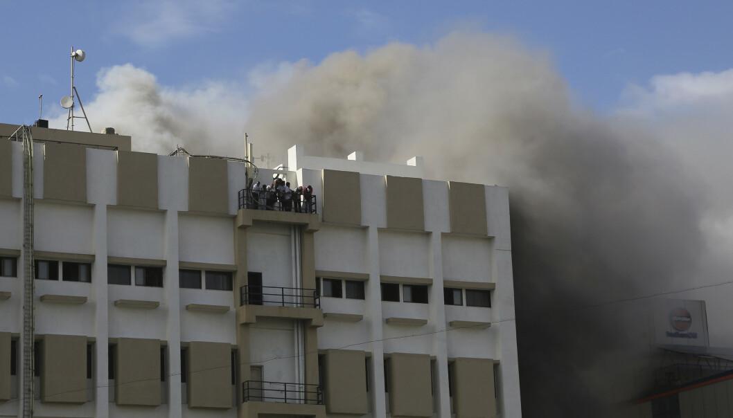 Folk venter på å bli reddet ned fra den brennende bygningen i Mumbai. Foto: Rafiq Maqbool / AP / NTB scanpix