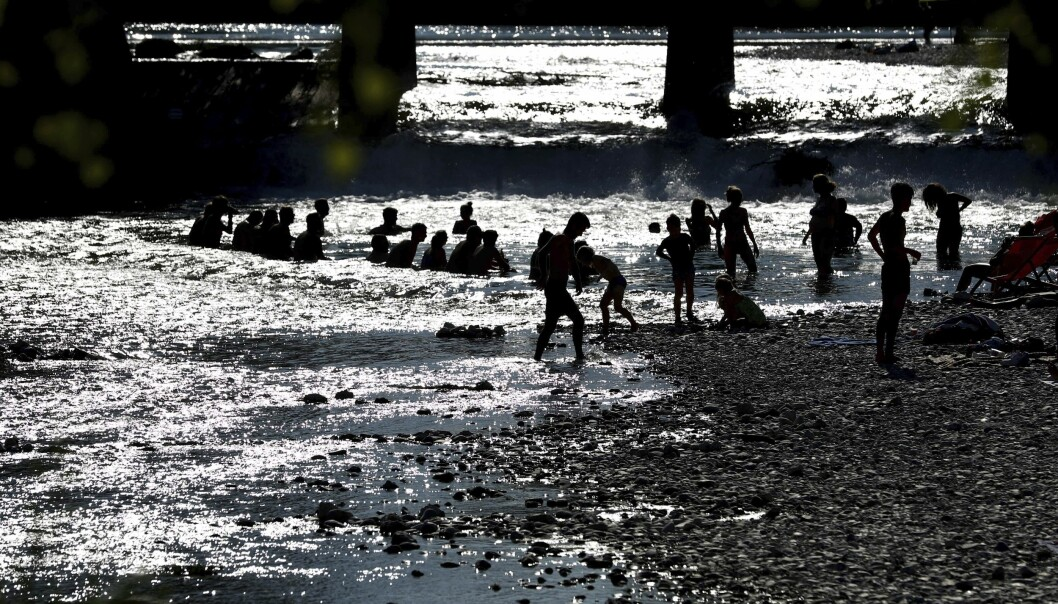 Folk bader i elven Isar i München torsdag. Foto: Matthias Schrader / AP / NTB scanpix