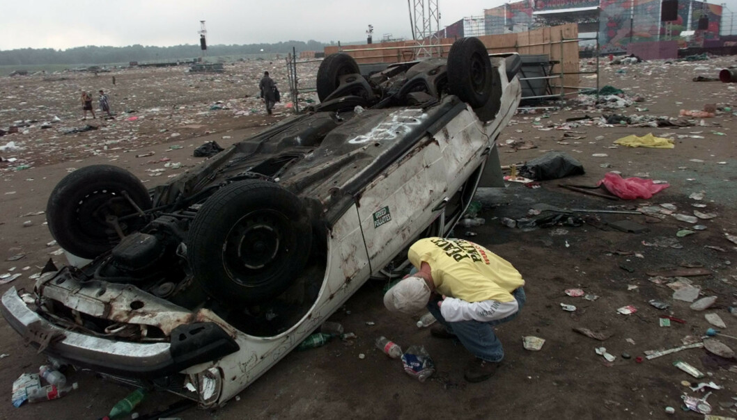DAGEN DERPÅ: En ansatt sjekker en utbrent bil foran scenen mandag morgen. Opptøyene varte gjennom natta. Foto: NTB scanpix