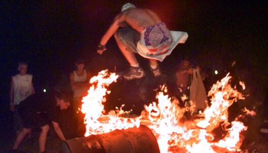 BRANNER: En publikummer hopper inn i en av de mange brannene som ble påtent. Foto: NTB scanpix