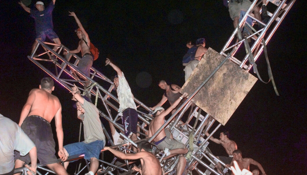 KLATRET OG REV NED: Publikum rev ned og klatret på et tårn ved scenen. Foto: Stephen Chernin/AP/NTB scanpix