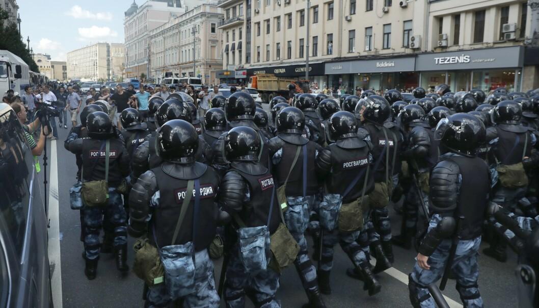 BLOKKERER: Politiet blokkerer en gate under protestene. AP / NTB Scanpix