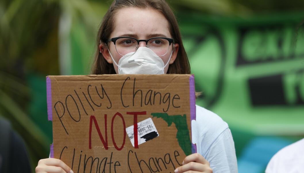 En tenåring demonstrerer i Miami i midten av juli hvor hun ber om politiske endringer, ikke klimaendringer. Foto: AP/ NTB scanpix.