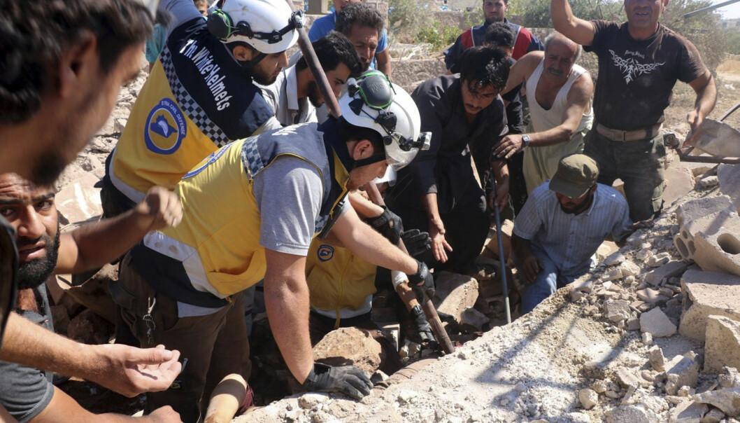 Redningsarbeidere fra gruppa Hvite hjelmer leter etter overlevende i ruinene av en bygning etter et luftangrep mot byen Kfar Rouma i Idlib-provinsen. Foto: AP / NTB scanpix