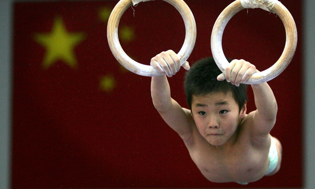A young Chinese athletes excercise at a gymnastic hall at the Beijing Shichahai sports school December 21, 2004. The school is the biggest sports boarding school in the Chinese capital and has a history of training the country's future Olympic hopefuls. REUTERS/Reinhard Krause
