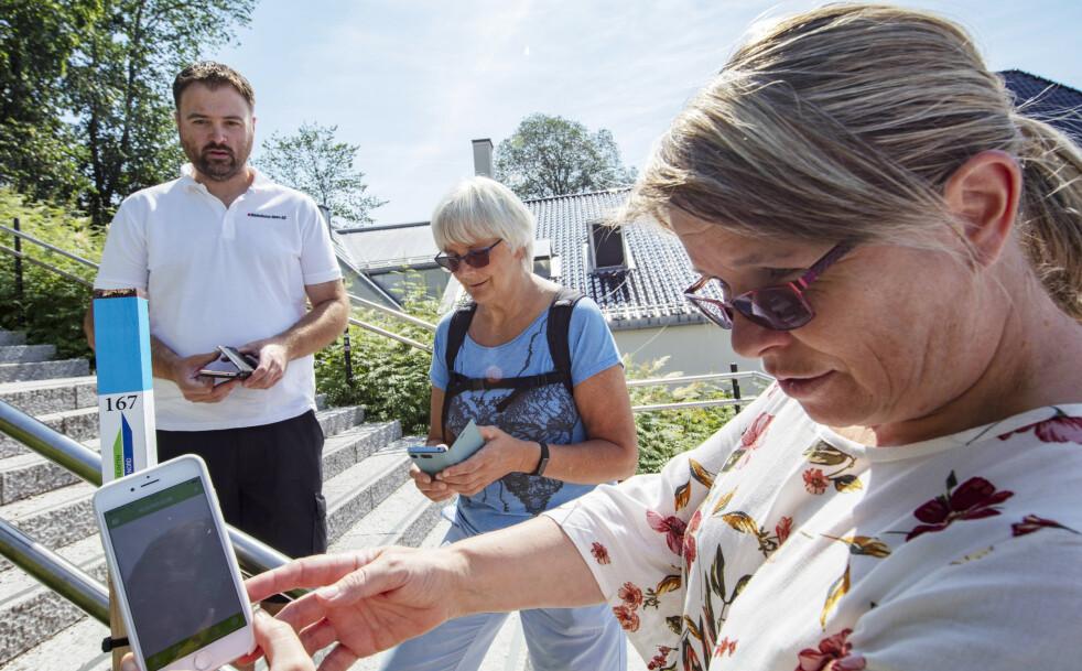QR-kode: Stolpejaktens mobil-app gjør det enkelt å registrere stolpefunnene. Her er Liv Langberg (57) i ferd med å scanne inn QR-koden. Geir-Arne Eriksen (39) og Mona Ekeheien (63) venter på tur. FOTO: Geir Olsen/NTB scanpix.