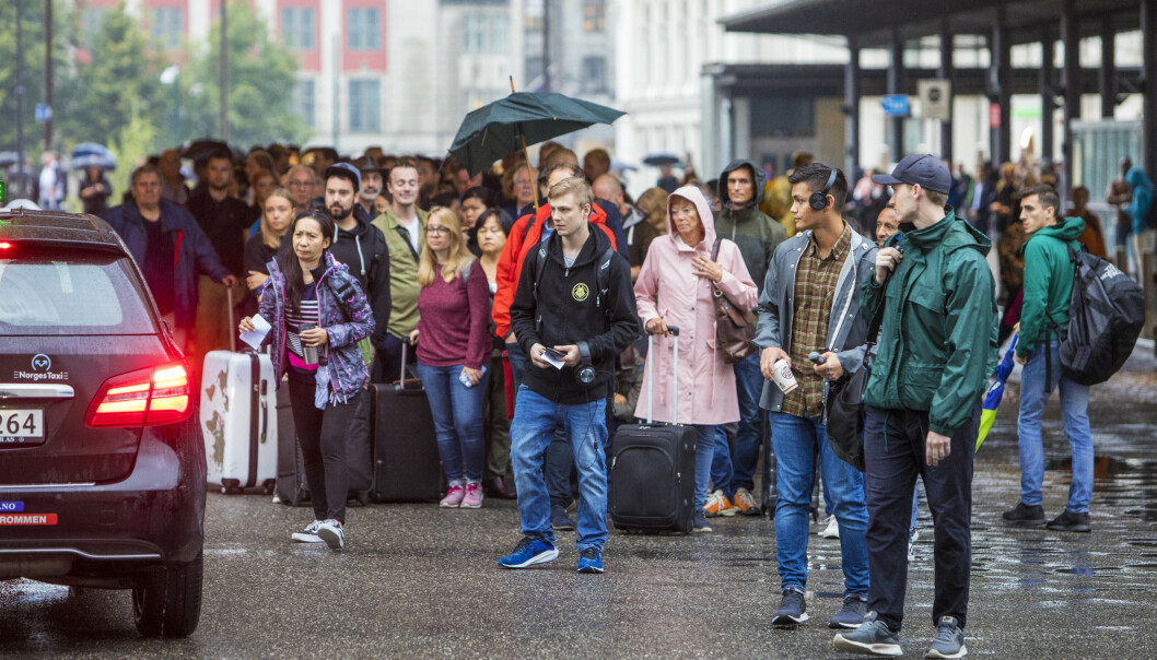 Passasjerer venter på taxi på Oslo S. Kraftig lyn og torden skaper togkaos på Østlandet. Vy melder at det ikke er nok alternativ transport til passasjene som vil benytte Østfoldbanen torsdag ettermiddag. Foto: Ole Berg-Rusten / NTB scanpix