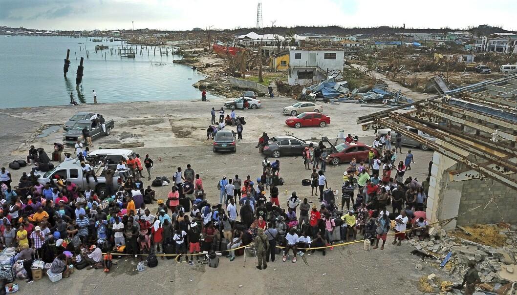 Folk samler seg på Marsh Harbour Port i Abaco på Bahamas i håp om å komme seg på en båt og vekk fra øya. Foto: Al Diaz / Miami Herald via AP / NTB scanpix