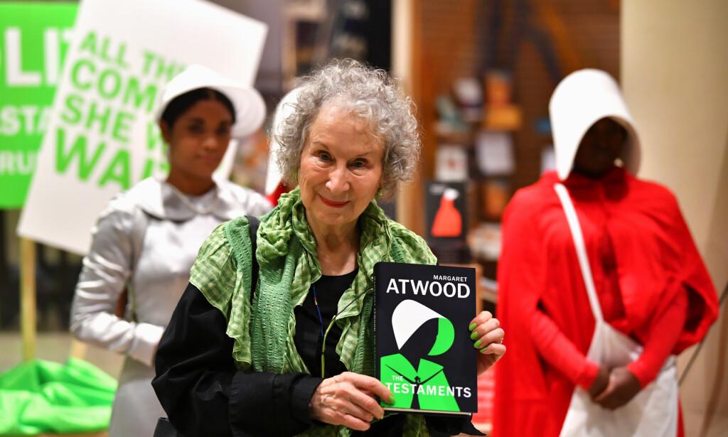 MED GILEADS DØTRE: Margaret Atwood lanserte sin nye roman i London i dag, i selskap med utkledde «tjenerinner» og andre døtre av Gilead. Foto: NTB SCANPIX