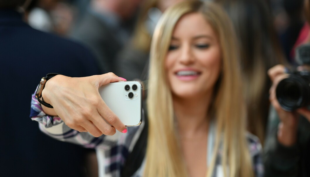 A woman tries out a new Apple 11 Pro during an Apple product launch event at Apple's headquarters in Cupertino, California on Tuesday, on September 10, 2019. - Apple unveiled its iPhone 11 models Tuesday, touting upgraded, ultra-wide cameras as it updated its popular smartphone lineup and cut its entry price to $699. (Photo by Josh Edelson / AFP)