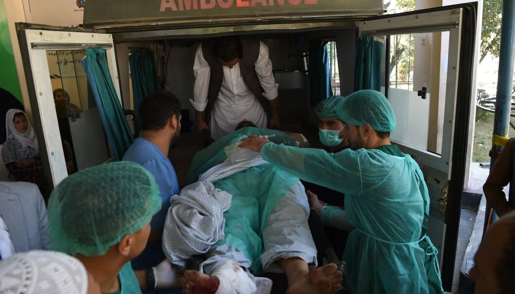En såret afghaner legges inn i sykebilen etter angrepet i Afghanistan 17. september. Foto: NTB scanpix / AFP