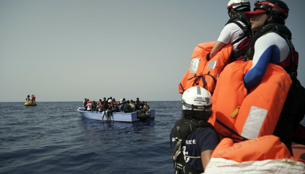 Redningsmannskap fra SOS Méditerranée står klar med redningsvester idet de er i ferd med å berge passasjerene fra en overfylt trebåt, rundt 100 kilometer fra Libyas kyst tirsdag. Foto: Renata Brito / AP / NTB scanpix