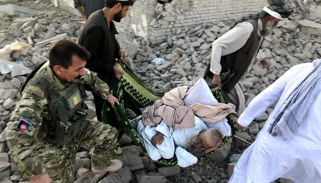 Afghanske sikkerhetsstyrker og frivillige bærer bort en såret mann etter bombeangrepet i provinshovedstaden i Zabul torsdag. Foto: Ahmad Wali Sarhadi / AP / NTB scanpix