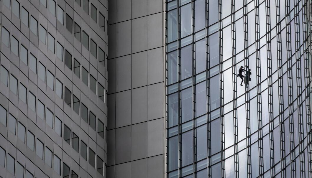 Franske Alain Robert brukte 30 minutter på å klatre opp den 154 meter høye bygningen «Skyper» i Frankfurt lørdag formiddag. Han klatret opp uten sikkerhetsutstyr. Foto: Michael Probst / AP / NTB scanpix