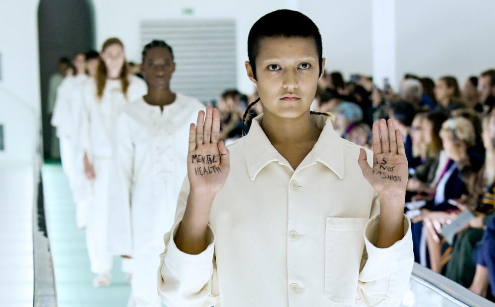 STUNT: Modellen Ayesha Tan-Jones gjennomførte en stille protest der hun hadde skrevet «Mental helse er ikke mote» i håndflatene. Foto: NTB Scanpix