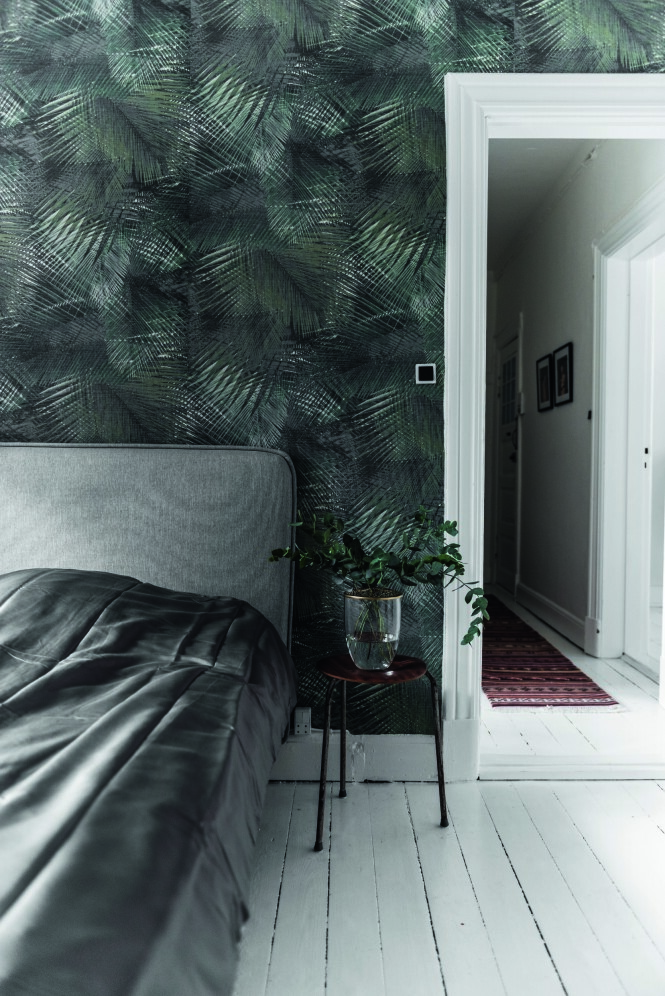 Soverommet har fått støvete farger i nyanser av grønt og grått, kombinert med detaljer i messing. En sengegavl skaper luksuriøs hotellstemning. Palmetapetet er fra Tapetforum, og vasen på bordet er fra Dims Studio. Tips! Skap en avslapningssone på soverommet med få møbler og dempede farger. FOTO: Benjamin Lee Rønning Lassen