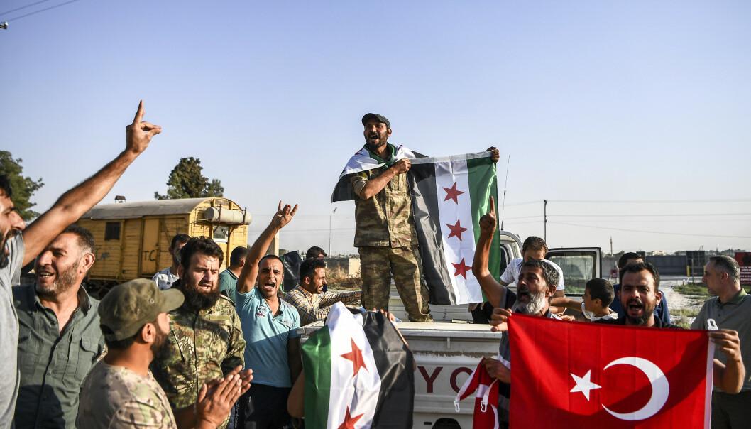 Tyrkisk-støttede syriske opprørere feirer i Sanliurfa-provinsen søndag etter meldinger om at tyrkiske styrker og alliert milits hadde erobret byen Tal Abyad fra kurdisk milits. Foto: Cavit Ozgul / AP / NTB scanpix