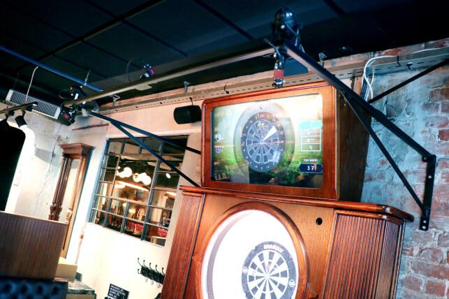 Her ser du de tre kameraene som ti ganger i sekundet sjekker hva som har skjedd på dartskiva, og skjermen over dartskiva som viser hva spilleren bør gjøre, og faktisk har gjort. 📸: Ole Petter Baugerød Stokke