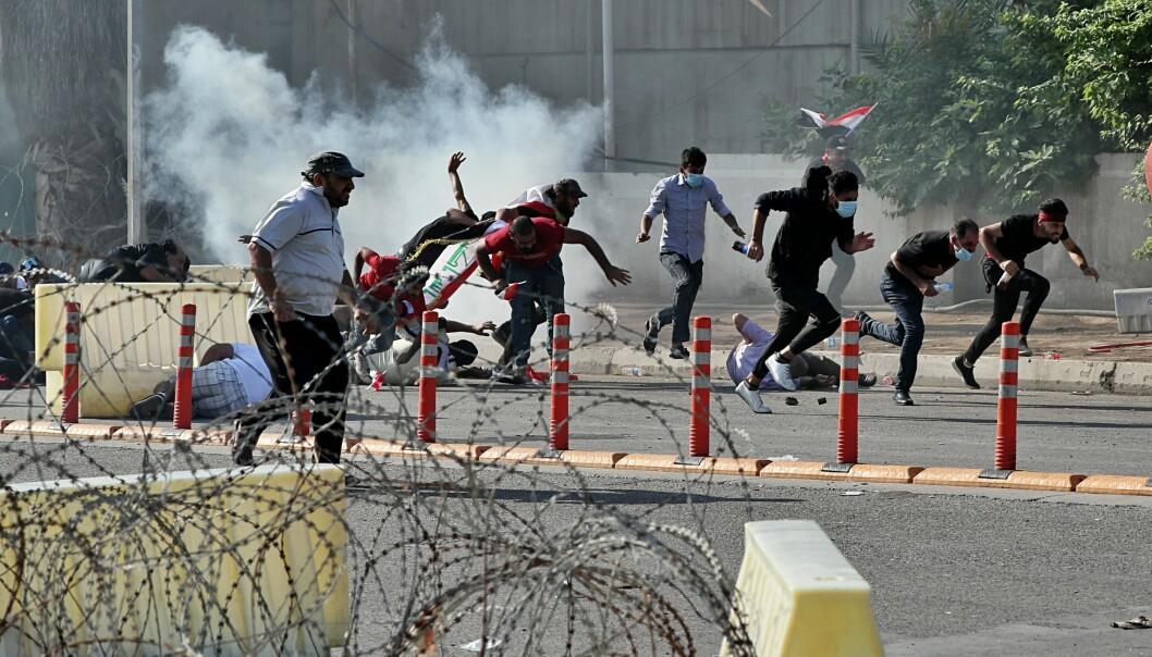 Demonstranter i Bagdad løper fra tåregass som irakiske sikkerhetsstyrker har sendt mot dem. Protestene mot regjeringen fortsatte fredag. Foto: AP / NTB scanpix